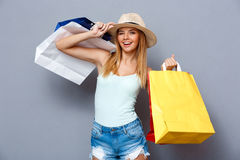 young beautiful girl holding colorful bags over gray background. Royalty Free Stock Photos