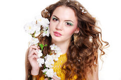 Young beautiful girl holding flowers. Young beautiful girl with blond curly hair holding flowers Royalty Free Stock Photo