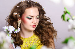 Young beautiful girl holding flowers. Young beautiful girl with blond curly hair holding flowers Royalty Free Stock Photos