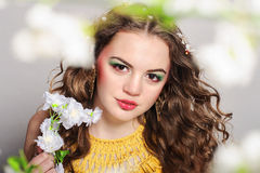 Young beautiful girl holding flowers. Young beautiful girl with blond curly hair holding flowers Royalty Free Stock Images