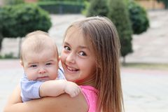 Young beautiful girl holding her little brother in her arms smiling happily and looking at camera stock photo