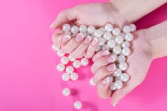 Young female holding many pearls in hand with french nails polish isolated on pink royalty free stock image