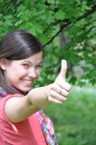 Young beautiful girl holding a thumb up. In a background of nature Stock Image