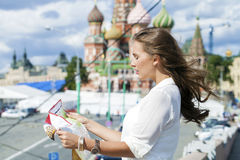 Young beautiful girl holding a tourist map of Moscow, Russia royalty free stock photos