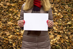 Young beautiful girl holding a white sheet of paper in her hands in the park. Royalty Free Stock Images