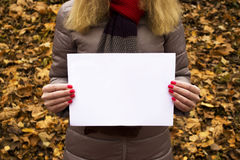 Young beautiful girl holding a white sheet of paper in her hands in the park. Stock Photos