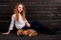 A young beautiful girl holding a wild fox animal that was traumatized by a man and rescued by her and now lives as before Royalty Free Stock Photos