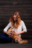 A young beautiful girl holding a wild fox animal that was traumatized by a man and rescued by her and now lives as before Stock Photography