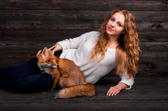 A young beautiful girl holding a wild fox animal that was traumatized by a man and rescued by her and now lives as before Stock Photo