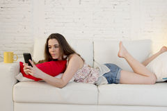 Young beautiful girl at home couch relaxed using mobile phone smiling happy and cheerful Stock Photo