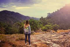 Young beautiful girl in the hoodie shirt and touristic backpack looking on amazing landscape from the mountain of Hemera, Turkey. stock image