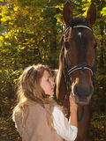 Young beautiful girl and a horse in the autumn for stock images