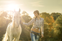 Young beautiful girl with a horse on the dry field royalty free stock photo