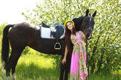 Young beautiful girl with a horse in garden Royalty Free Stock Image