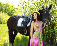 Young beautiful girl with a horse in garden Stock Photo