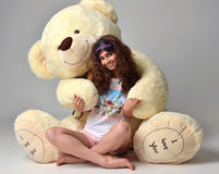 Young beautiful girl hugging big teddy bear soft toy happy smiling. On grey background royalty free stock image