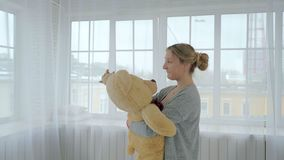Young and beautiful girl hugging a teddy bear in a bright city room. stock video