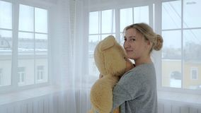Young and beautiful girl hugging a teddy bear in a bright city room. stock video footage