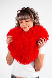Young beautiful girl  hugs a big soft heart. Royalty Free Stock Photography