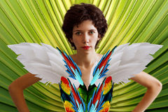 Young beautiful girl in the image of a parrot in a brightly colored feathers and wings. A woman in a tropical jungle. Fantastic image Royalty Free Stock Photo