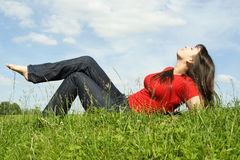 Young Beautiful Girl In Red Shirt Lies On Grass Royalty Free Stock Images