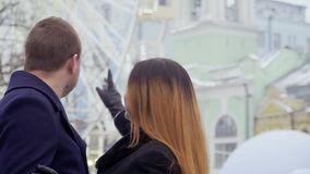 Young beautiful girl invites her boyfriend to ride on ferris wheel. Happy in love couple spend their leisure time together walking in the amusement park stock footage