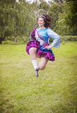 Young beautiful girl in irish dance dress jumping outdoor Royalty Free Stock Images