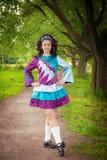 Young beautiful girl in irish dance dress posing outdoor. Young beautiful girl in irish dance dress and wig posing outdoor Stock Image