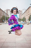 Young beautiful girl in irish dance dress and wig jumping Royalty Free Stock Photo