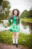 Young beautiful girl in irish dance dress and wig posing. Outdoor Royalty Free Stock Image