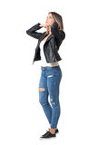 Young beautiful girl in jeans and leather jacket adjusting hair. Full body length portrait isolated over white background stock image