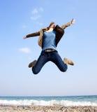 Young beautiful girl jumping at the beach. Stock Photos