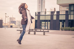 Young beautiful girl jumping in the city streets Royalty Free Stock Images