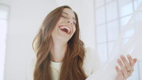 Young beautiful girl laughing in white decor. Slow motion. stock video footage