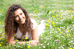 Young beautiful girl laying on the daisy flowers field, outdoor Royalty Free Stock Photos