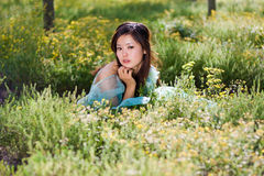 Young beautiful girl laying on the flowers field Royalty Free Stock Photography