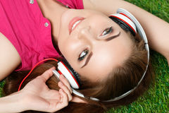 Young beautiful girl laying on the grass in park listening to mu Stock Photography