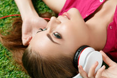 Young beautiful girl laying on the grass in park listening to mu Stock Images