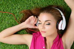 Young beautiful girl laying on the grass in park listening to mu Royalty Free Stock Image