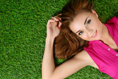 Young beautiful girl laying on the grass in park Royalty Free Stock Photos