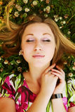 Young beautiful girl lays on a grass Stock Photos