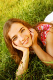 Young beautiful girl lays on a grass royalty free stock images