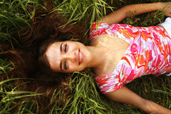 Young beautiful girl lays on a grass Stock Photography