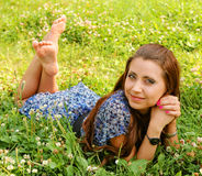 Young beautiful girl lays on a grass Stock Photos
