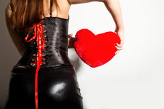 Young beautiful girl in a leather corset with lacing and skirt, holding red heart pillow Royalty Free Stock Images