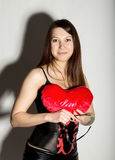 Young beautiful girl in a leather corset with lacing and skirt, holding red heart pillow Royalty Free Stock Image