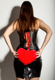 Young beautiful girl in a leather corset with lacing and skirt, holding red heart pillow Stock Photos