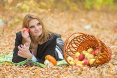 Young beautiful girl lies on the on the foliage in the autumn forest and dreaming holding an apple and looking to the right Stock Photos