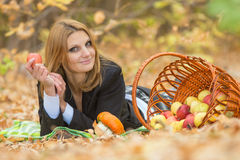 Young beautiful girl lies on the on the foliage in the autumn forest and holding an apple in her hand Royalty Free Stock Photo