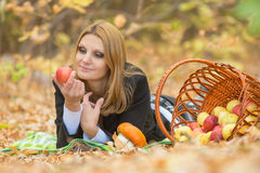 Young beautiful girl lies on the on the foliage in autumn forest and looking at an apple in her hand Royalty Free Stock Images